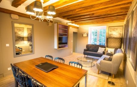 Confortable salon de l'appartement Elisabeth avec grande table, télévision HD et canapés.