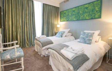 Chambre confortable avec deux lits simples de l'appartement Angélique